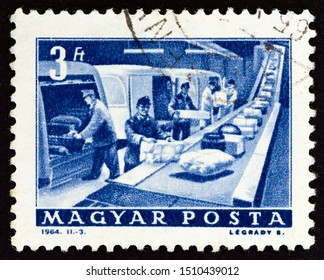 """HUNGARY - CIRCA 1964: A stamp printed in Hungary from the """"Transport and Communications"""" issue shows Post Office parcel conveyor, circa 1964."""
