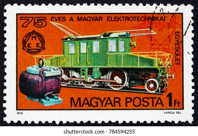 HUNGARY - CIRCA 1975: a stamp printed in Hungary shows early transformer, Kando locomotive, 1902, pylon, 75th anniversary of Hungarian Electrotechnical Association, circa 1975