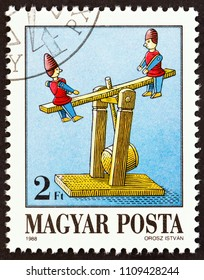 """HUNGARY - CIRCA 1988: A stamp printed in Hungary from the """"Exhibits in Toy Museum, Kecskemet"""" issue shows See-saw, circa 1988."""
