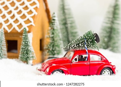 Hungary - December, 2018: Red miniature toy car holding a christmas tree on artifical snow. Gingerbread house and trees in the background.