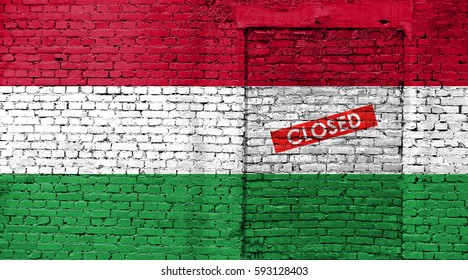 Hungary flag on brick wall with bricked door and Closed sign