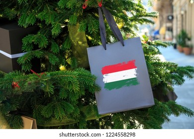 Hungary flag printed on a Christmas shopping bag. Close up of a gift bag as a decoration on a Xmas tree on a street. New Year or Christmas shopping, local market sale and deals concept.