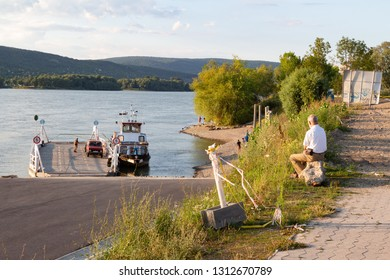 Visegrád / Hungary - July 26 2018: Man sitting on riverside of Danube looking at arriving ferryboat