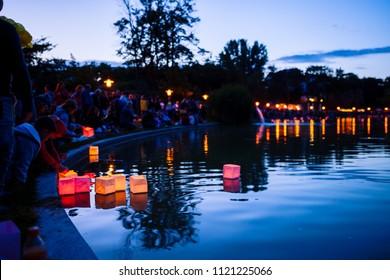 Gyömrő, Hungary - Jun 23, 2018: People take wish lanterns with burning candles to the lake on summer night.