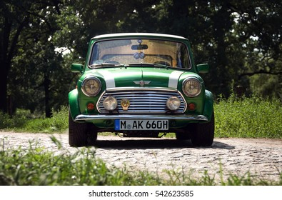 HUNGARY - May, 2012: Green classic Austin Mini Cooper retro vehicle parked on the road against the background of a forest at the International Mini Meeting 2012 in HUNGARY.