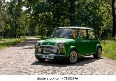 HUNGARY - May, 2012: Green classic Austin Mini Cooper retro vehicle parked on the road against the background of a forest at the International Mini Meeting 2012. Automotive photography. Retro car.