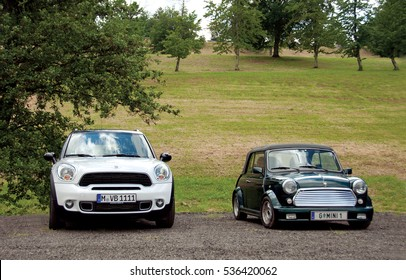 HUNGARY - May, 2012: Mini Countryman and classic Austin Mini Cooper retro vehicle parked against the background of a green hill at the International Mini Meeting 2012 in HUNGARY. New and old Mini.