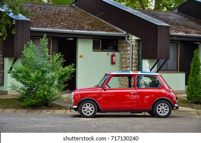 HUNGARY - May, 2012: Red classic Austin Mini Cooper retro vehicle parked on the road against the background of a house at the International Mini Meeting 2012. Automotive photography. Retro car.