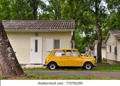 HUNGARY - May, 2012: yellow classic Austin Mini Cooper retro vehicle parked on the green lawn near the house at the International Mini Meeting 2012 in HUNGARY.