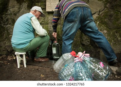 Visegrád, Hungary - September 12, 2017: Two men fill up their plastic bottles with fresh and clean water from the mountain at Kaán-Forrás.