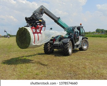HUNGARY, TISZACSEGE - May 8, 2018: Kramer telehandler lifting a packed bale with a bale handler.