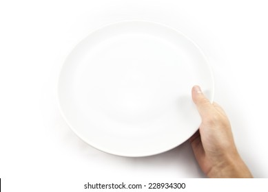 Hunger concept. Man holding empty plate waiting for food isolated on white from top view.