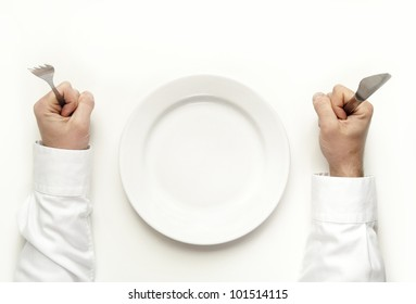 Hunger concept. Man holding fork and knife waiting for food isolated on white from top view.