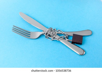 Hunger strike as a diet for weight loss. Fork and knife are wrapped in chain and locked against blue background.