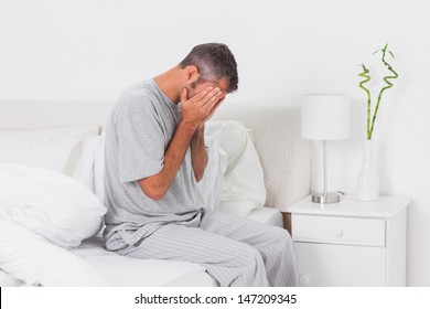 Hungover man holding his head in bed