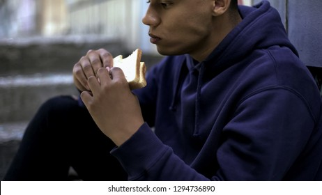 Hungry afro-american teenager eagerly eating sandwich, poor family, crisis
