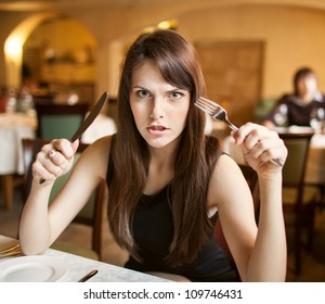 hungry and angry female person at restaurant holding fork and knife