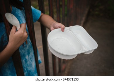a hungry asian child holding an empty bowl.