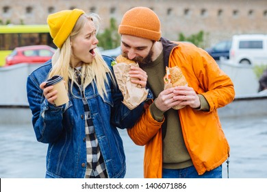 Hungry beard man taking croissants out of woman and biting it with greed at city street. I dont believe you. Shocked emotional blond woman try to give back, gazes with stupefaction. Reaction concept