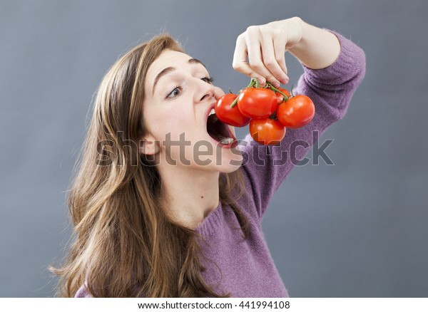 hungry beautiful young girl holding and eating up a tomato grape with appetite and greed for healthy vegetarian diet and nutrition, indoors