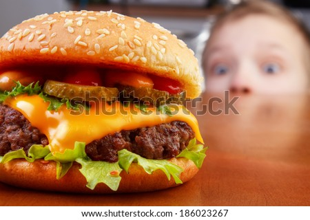 Hungry boy is staring and smelling a burger on wooden table