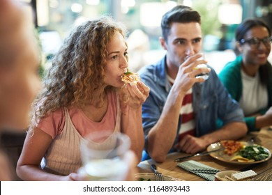 Hungry casual girl eating pizza by dinner among her friends and listening to one of them during chat