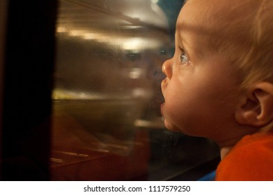 Hungry Caucasian Toddler Stares Longingly Into Over With Mouth On Door