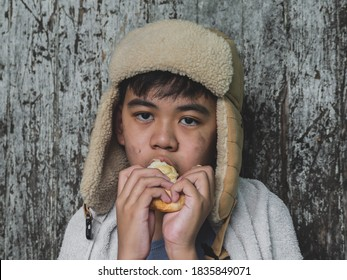 Hungry child eating bread that asking help for food donation from the people on street at the city. Unidentified homeless child begging on street. Shelter concept.