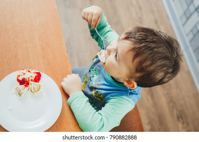 A hungry child is eating dumplings in the kitchen sitting in a chair in a white t-shirt