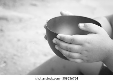 a hungry children holding an empty bowl, black and white style