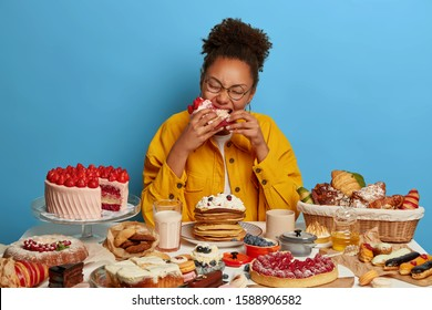Hungry curly African American woman bites big piece of cake, feels temptation after diet, sits at table overloaded with sweet dishes, loves desserts, being sweettooth or glutton, poses indoor
