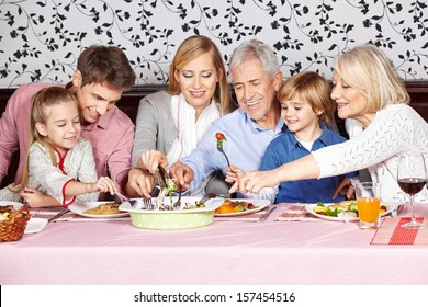 Hungry family reaching for food at dinner table at the same time