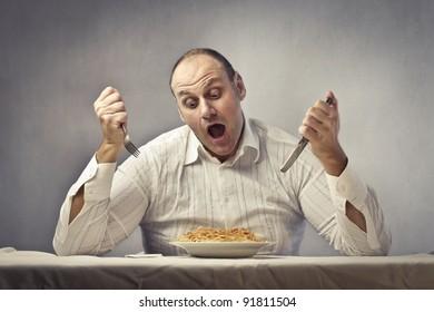 Hungry fat man eating spaghetti