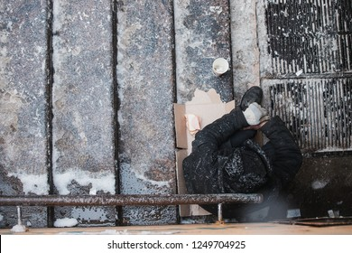 hungry freezing homeless man sitting on the steps at the entrance to the underpass with outstretched hand, cold weather, winter snow, begging, help and compassion, frostbite vagrants, dirty, pitiful