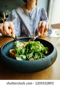Hungry French woman eating delicious green gourmand organic salad in Restaurant using fork and knife