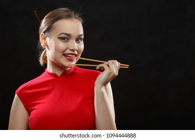 hungry fun beautiful woman in red dress with chopsticks on black background