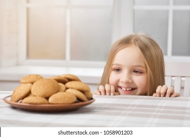 Hungry girl with blonde straight hair is looking on delicious cookies on table. Child looks nice and happy. She has beatiful smile. Close up was made on white window background.