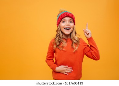Hungry Happy Young girl in sweater and hat holding her tummy and having idea while looking at the camera over orange background