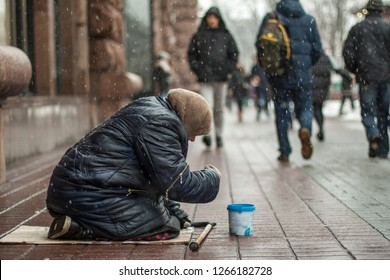 Hungry homeless beggar woman beg for money on the urban street in the city from people walking by