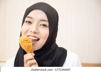 hungry islamic woman looking, eating halal fried chicken drumstick; concept of delicious halal food, fast food, health care, eating habit, crispy tasty fried chicken burger; asian muslim woman model
