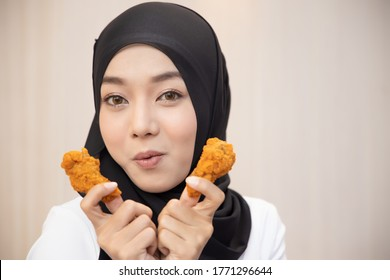 hungry islamic woman looking, eating halal fried chicken wingstick; concept of delicious halal food, fast food, health care, eating habit, crispy tasty fried chicken burger; asian muslim woman model