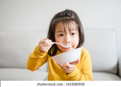 Hungry little asian girl eating rice with salmon teriyaki and watching TV in sofa at home.Happy meal and Delicious asian food concept.