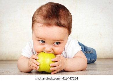 Hungry little baby boy eating apple