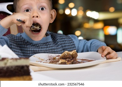 Hungry little boy gobbling down a slice of tasty chocolate cake with his mouth open wide for a mouthful as he sits at a table in a restaurant