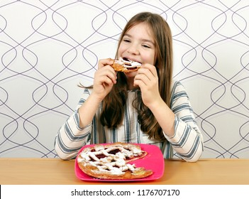 hungry little girl eats a pie with cherries