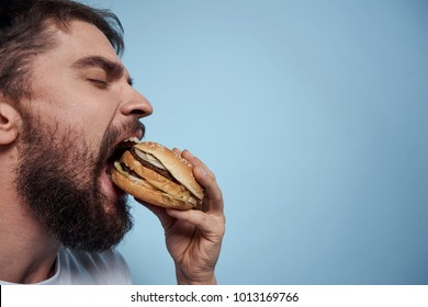 hungry man eating a burger on a blue background