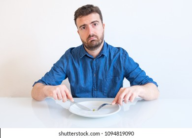 Hungry man feeling sad in front of a dish with a cabbage