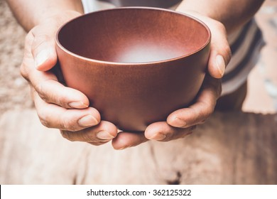 a hungry man holding an empty bowl