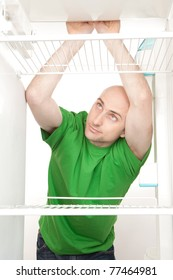 A hungry man leans on a shelf looking for food in an empty fridge.