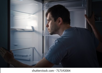 Hungry man is looking for food in empty fridge at night.